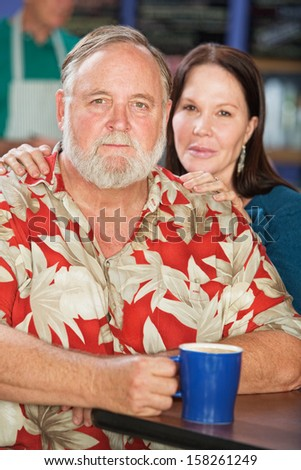 Attractive middle aged couple with coffee in cafe - stock photo