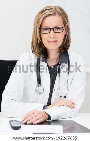 Attractive middle-aged female doctor wearing glasses and a stethoscope sitting at her desk looking directly at the camera with a smile - stock photo