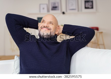 Attractive middle-aged man with a goatee sitting daydreaming as he relaxes at home staring up into the air with a smile of pleasure - stock photo