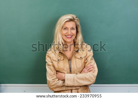 Attractive middle-aged teacher with a lovely smile standing with folded arms in front of the class blackboard - stock photo
