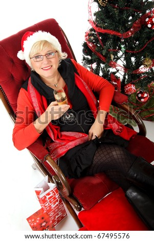 Attractive middle aged woman in Santa hat on sofa having a glass of champagne. Christmas tree beside. View from high corner. Studio shot. White background.