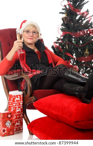 Attractive middle aged woman in Santa hat on sofa having a glass of champagne. Christmas tree beside. Studio shot. White background. - stock photo