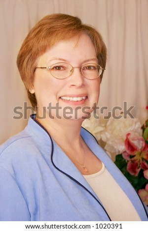 Attractive middle-aged woman in traditional pose over taupe backdrop with floral. - stock photo