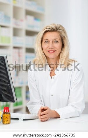 Attractive middle-aged woman pharmacist standing at the counter in the pharmacy behind a computer looking at the camera - stock photo