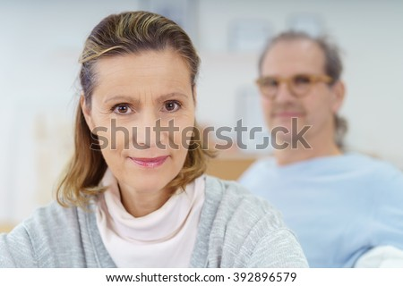 Attractive middle-aged woman relaxing at home with her husband looking into the camera with a smile, close up of her face - stock photo
