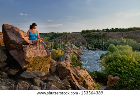Attractive middle-aged woman sitting cross-legged meditating on a rock above a mountain valley and river as she enjoys the tranquillity of nature - stock photo