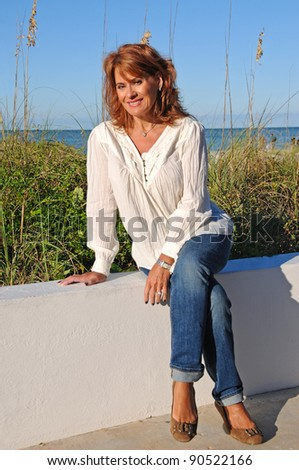 Attractive Middle Aged Woman Sitting on Wall - stock photo