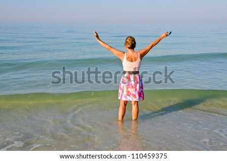 Attractive Middle Aged Woman Standing in the Ocean With Her Arms Held Up - stock photo