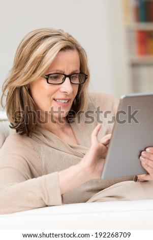 Attractive middle-aged woman using a tablet-pc sitting on a couch at home navigating the touchscreen with her finger - stock photo
