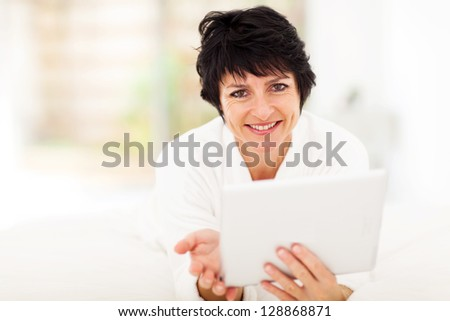 attractive middle aged woman using tablet computer at home - stock photo