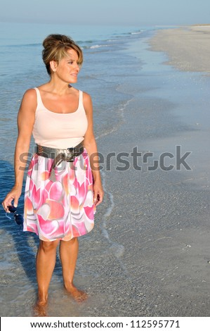 Attractive Middle Aged Woman Walking on the Beach in a Summer Dress - stock photo