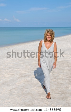Attractive Middle Aged Woman Walking on the Beach in a Sundress - stock photo