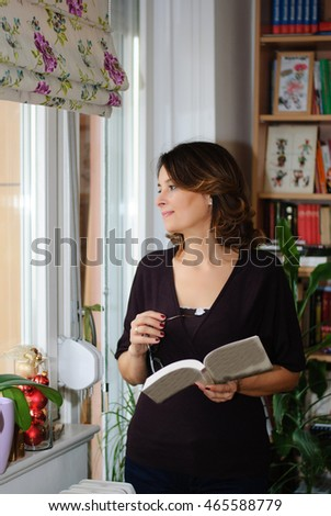 Attractive middle-aged woman wearing glasses stands, reading a book in her living room