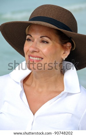 Attractive Middle Aged Woman Wearing Summer Hat - stock photo