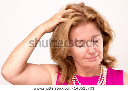 Attractive middle aged woman with a headache clutching her hand to the top of her head with downcast eyes and a serious pained expression, isolated on white - stock photo