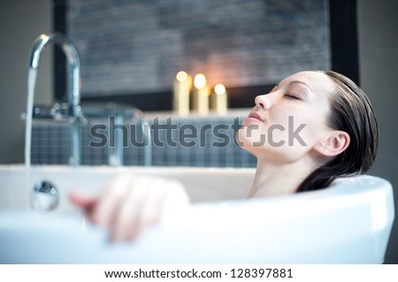 Attractive mixed asian woman relaxing in bath - stock photo