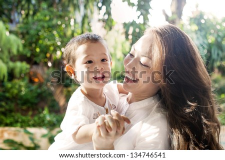 Attractive mixed female lifestyle spending time with happy child - stock photo