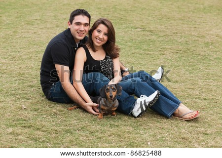Attractive mixed race couple with family dog in a park setting. - stock photo