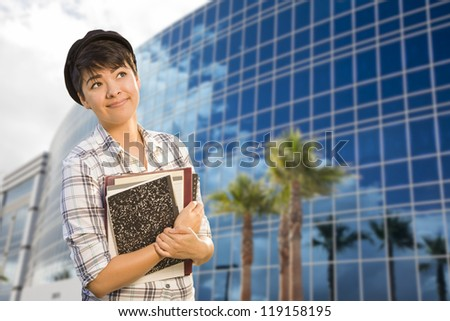 Attractive Mixed Race Female Student Holding Books in Front of Building. - stock photo