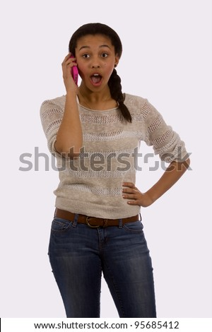 Attractive mixed race mulatto teen age girl wearing jeans with an oped-mouthed shocked expression talking on a cell phone - stock photo