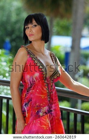Attractive model in a red pattern summer dress - stock photo