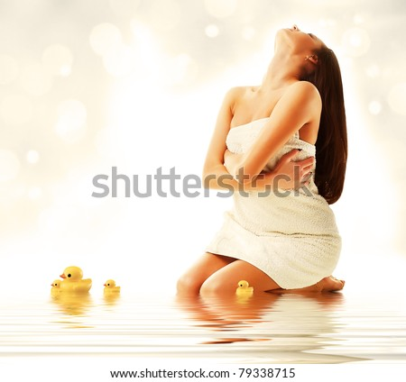 Attractive model in fresh white towel with ducks - stock photo