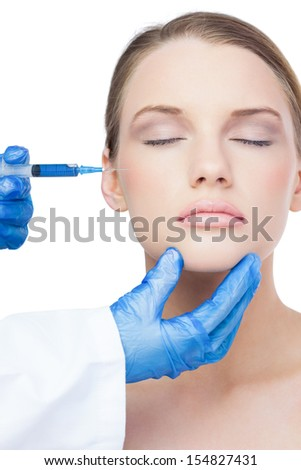 Attractive model on white background having an injection on the cheek