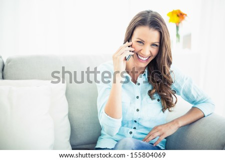 Attractive model sitting on cosy couch in bright living room having a phone call - stock photo