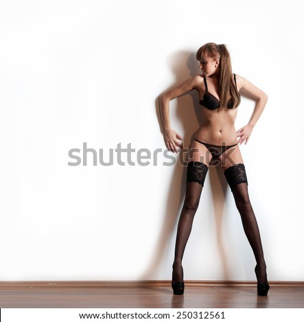 Attractive model with pantyhose and black lingerie standing on white wall. Fashion portrait of sensual long legs woman - indoor shoot. Sensual female in pantyhose posing provocatively. - stock photo