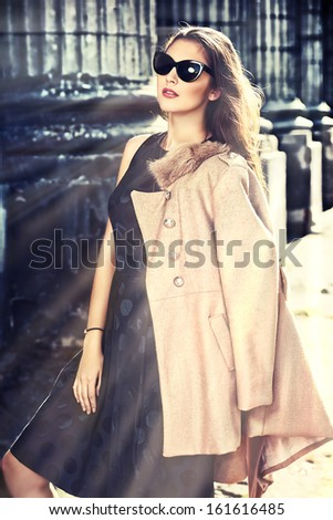 Attractive modern woman standing on the city street. - stock photo