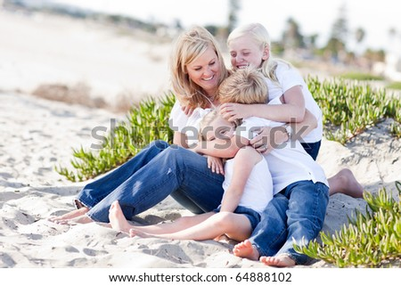 Attractive Mom Having Fun with Her Cute Children at The Beach. - stock photo