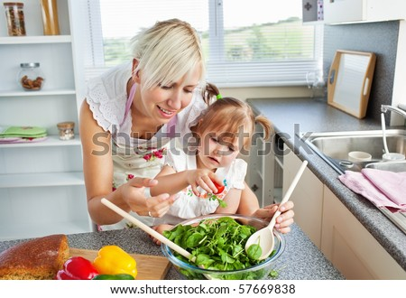Attractive mother and child cooking in the kitchen - stock photo