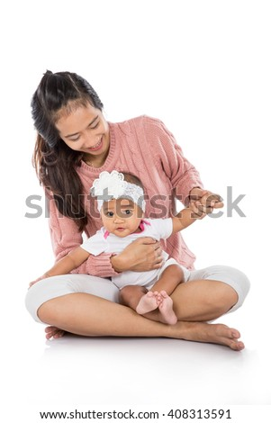 attractive mother holding her baby girl while sitting on a floor