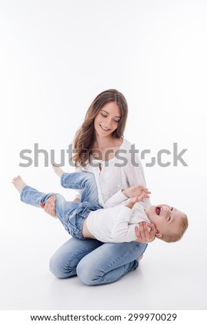 Attractive mother is sitting and holding her son. The boy is lying on female knees and laughing playfully. The lady is smiling and looking at him with love. Isolated on background - stock photo
