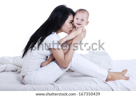 Attractive mother kissed her baby on the bedroom. isolated on white - stock photo