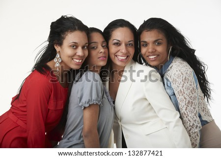 Attractive mother wearing white suit standing with her three teenage daughters in casual studio portrait. - stock photo