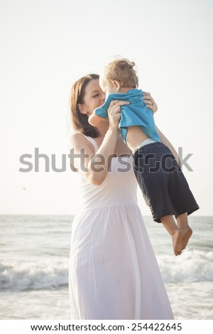 attractive mother with young son playing at the beach laughing - stock photo