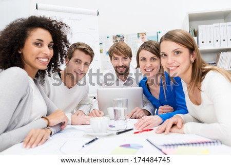 Attractive motivated young multiethnic business team sitting around a table in the office having a meeting with the team leader - stock photo