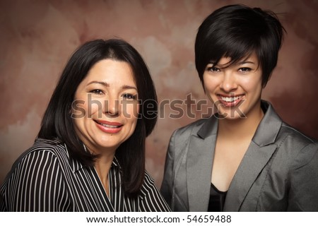 Attractive Multiethnic Mother and Daughter Studio Portrait on a Muslin Background. - stock photo