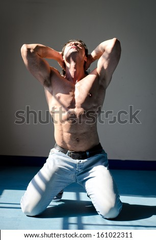 Attractive muscleman kneeling shirtless on grey background with hands behind head, looking up - stock photo