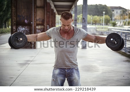 Attractive Muscular Hunk Man Lifting Weights Outdoor, Looking Down for the Effort - stock photo