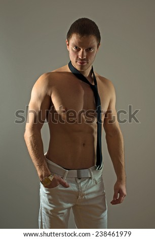 Attractive muscular man posing with tie.