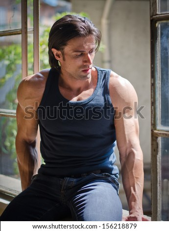 Attractive, muscular man sitting on open window looking down, wearing dark tanktop - stock photo