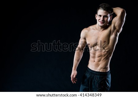 Attractive muscular young man looking to the camera and smiling with arm up, hand behind head, isolated on black background - stock photo