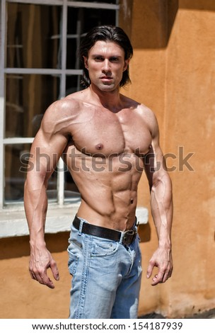 Attractive muscular young man shirtless wearing jeans outdoors - stock photo