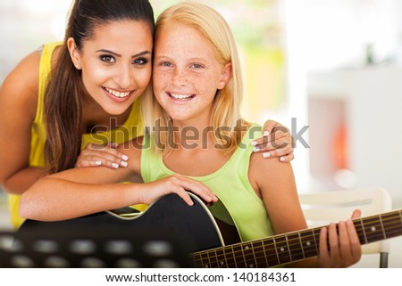 attractive music tutor and preteen girl with a guitar - stock photo