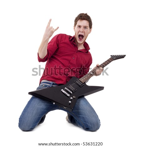 Attractive musician playing guitar on his knees and making a rock and roll gesture over white - stock photo