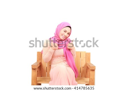 Attractive Muslim woman with scarf showing thumbs up - stock photo