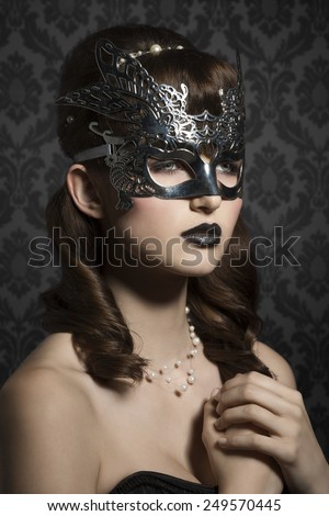 Attractive, mysterious, woman with silver, carnival mask and very dark make up. She looks very elegant and romantic. - stock photo