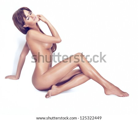 Attractive naked brunette beauty with clean skin sitting in the sunny light - stock photo